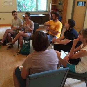 Deep Canvassers sit in a semi-circle and debrief about their experiences